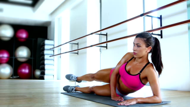 Woman athlete working out kneeling on a gym mat raising her leg backwards in the air video