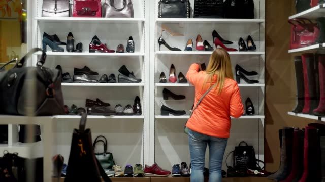 Woman back in a shoe store, chooses his boots and shoes. Woman back in a shoe store, chooses his boots and shoes. Through the glass shooting rack stock videos & royalty-free footage