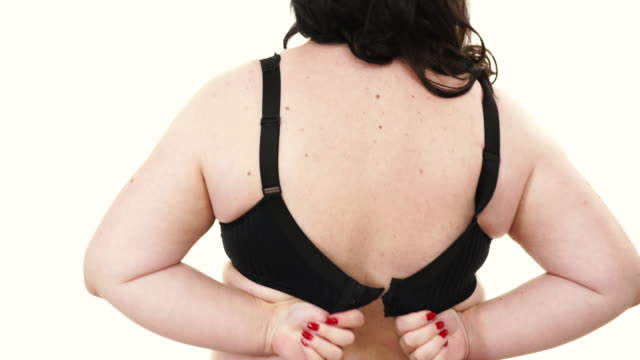 Woman back view putting on her bra lingerie video