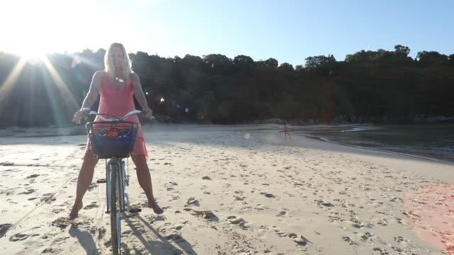 Woman balances on bicycle, on tropical beach video