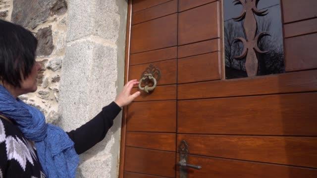 A woman bangs a knocker and retreats