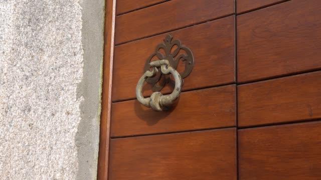 woman  bangs a knocker three times