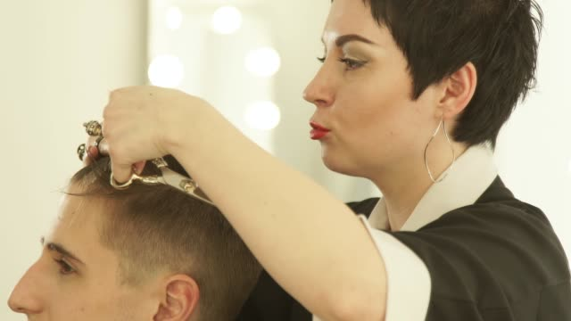 Woman barber combing and cutting hair with professional scissors in hairdressing salon. Close up hairdresser doing hairstyle with hairdressing scissors and comb in barber shop video