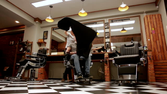 A woman Barber in the barbershop shop to put customer's man in a chair and begins to conduct his haircut. The value video