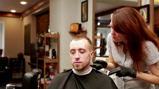 A woman Barber in the barbershop shop to put customer's man in a chair and begins to conduct his haircut video