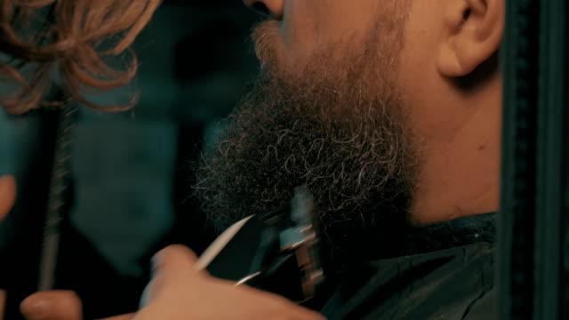 Woman barber trimming beard video