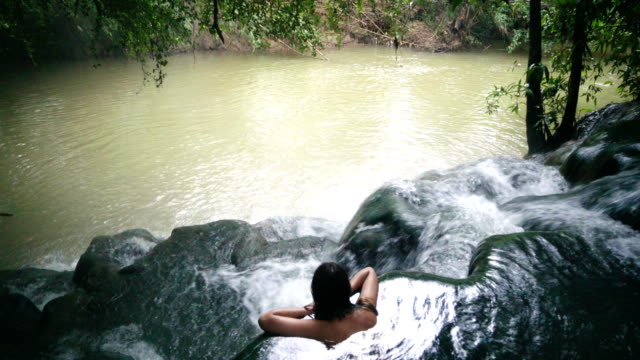 Woman bathing in hot spring waterfall video