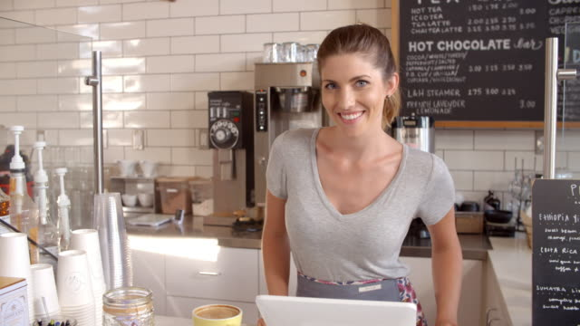 Woman behind the counter of a coffee shop crosses arms video