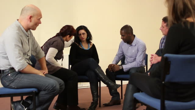 Woman being consoled in small group counselling therapy video