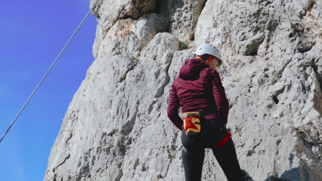 Woman belaying from the cliff and high-five to her instructor on the ground