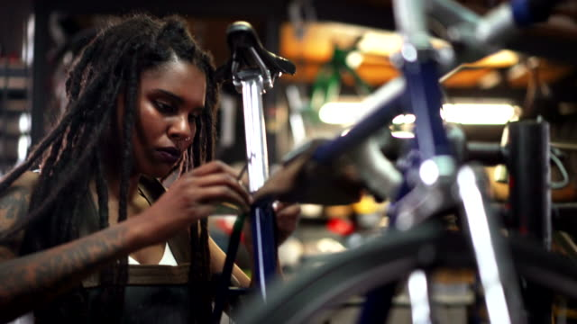Woman bicycle mechanic fixing a wheel in a repair workshop Afro-american woman with dreads and tattoos fixing a bicycle wheel in her repair workshop where she works as a skilled bike mechanic locs hairstyle stock videos & royalty-free footage