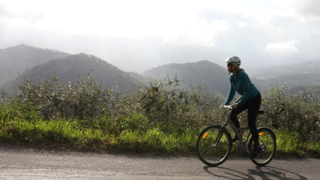 Woman bicycles along rural road above hills, olive groves  pedal pushers stock videos & royalty-free footage