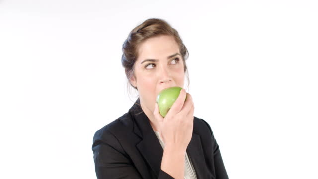 Woman biting and eating an apple on a white studio background video