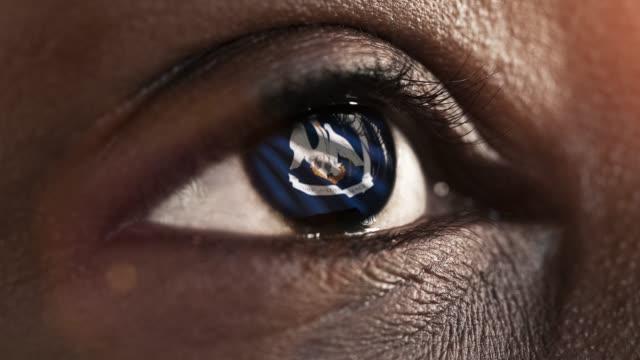 vidéos et rushes de oeil noir de femme dans le gros plan avec le drapeau de l'état de louisiane dans l'iris, états unis de l'amérique avec le mouvement de vent. concept vidéo - démocratie