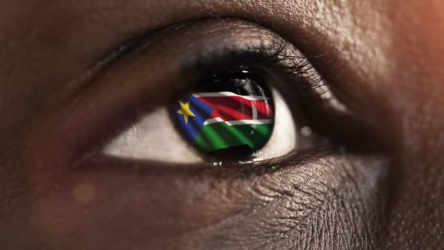 woman black eye in close up with the flag south sudan in iris with wind motion. video concept - sudan del sud video stock e b–roll