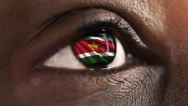 woman black eye in close up with the flag Suriname in iris with wind motion. video concept
