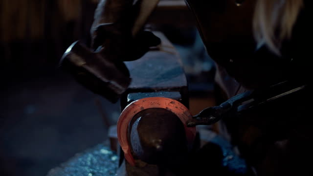 Woman blacksmith forges a horseshoe. video