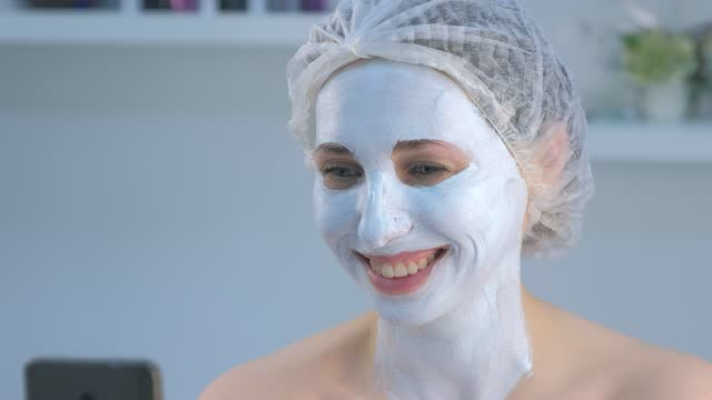 Woman blogger making selfie with facial mask on mobile phone in beauty clinic. video