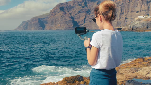 여자 금발 블로거 인플루언서가 짐벌 안정기를 사용하여 스마트 폰에서 비디오에서 서핑을 촬영합니다. 바다의 화산 해안에. 소셜 네트워크용 콘텐츠 제작의 개념 - 영화 촬영 스톡 비디오 및 b-롤 화면