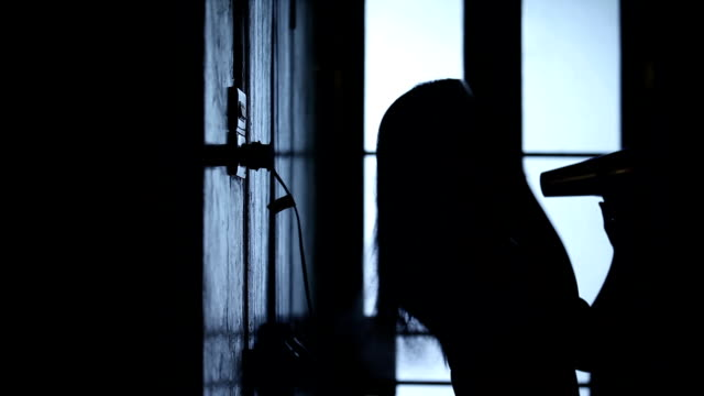 Woman Blow Drying Hair with a hairdryer in Silhouette video