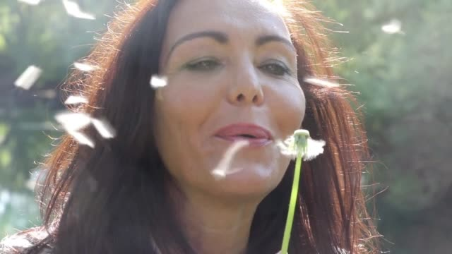 Woman blowing dandelion Woman smiling after she blows all of the dandelion seeds away. In nature, blurred background. Sunlit backlit. donna stock videos & royalty-free footage