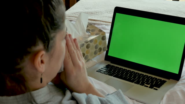 woman blowing her nose with a green screen computer nodding her head yes - telemedicine stock videos & royalty-free footage
