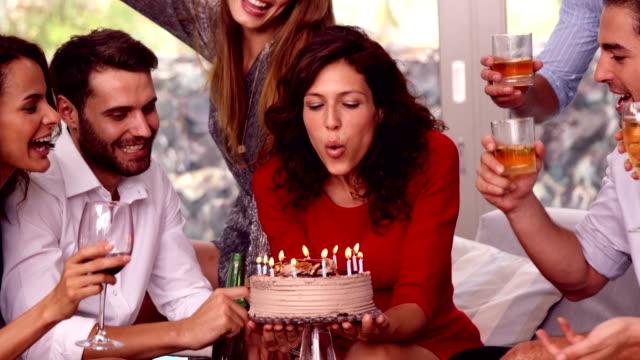 woman blowing z świeca na jej tort urodzinowy - 20 29 lat filmów i materiałów b-roll