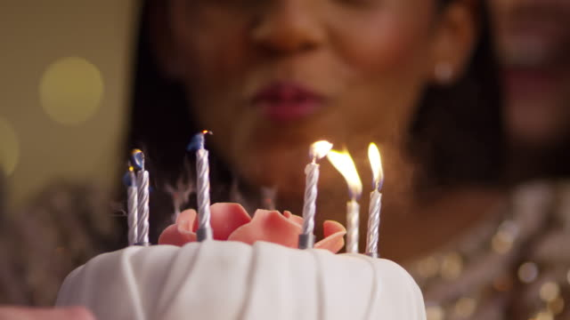 Woman Blowing Out Candles On Birthday Cake video