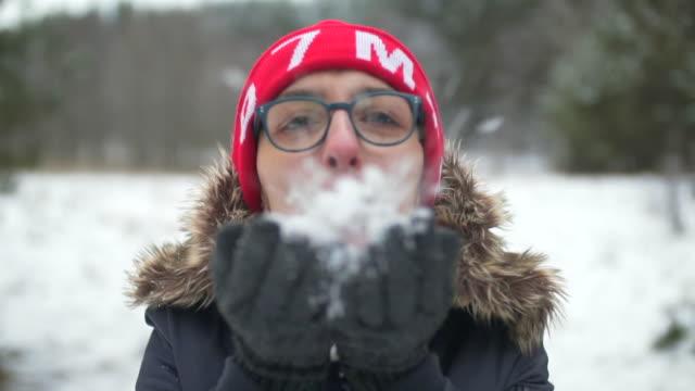 kvinna blåser snöflingor i vinterlandskap - blåsa en kyss bildbanksvideor och videomaterial från bakom kulisserna