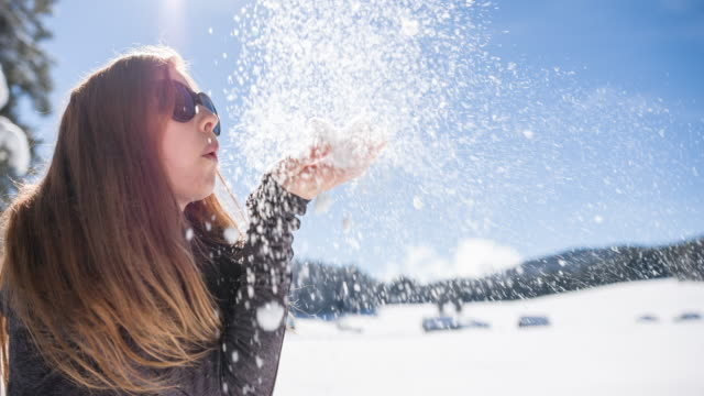 Woman blowing snowflakes in winter landscape video