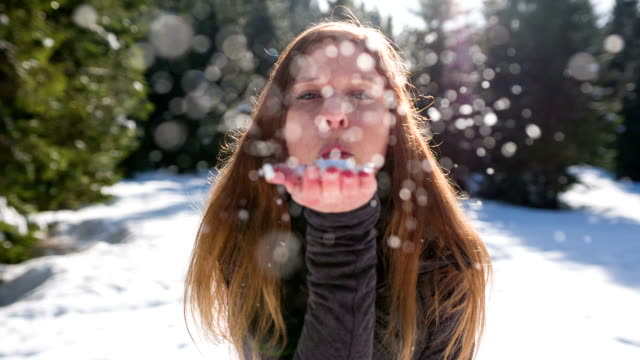 Woman blowing snowflakes video