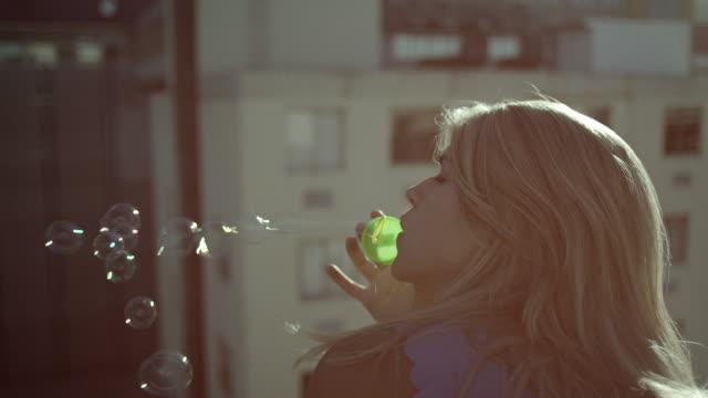 Woman blowing soap bubbles video