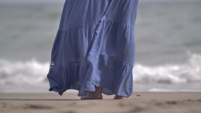 Woman blue skirt develops in the wind on the coast video