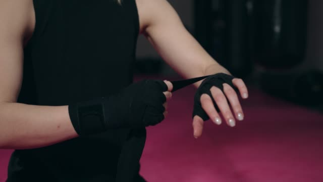 Woman boxer dressed in black sports clothing wrapping up her hands video