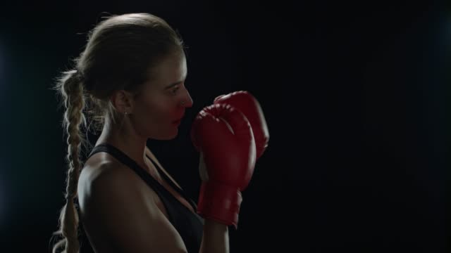 Woman boxer kicking air in slow motion. Woman fighter training punch