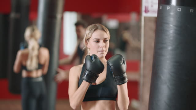 woman boxer training punches on boxing training with coach together. - kick boxing video stock e b–roll