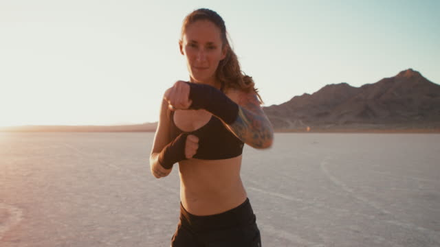 woman boxing at sunset outside in desert punching at camera - colpire con un pugno video stock e b–roll