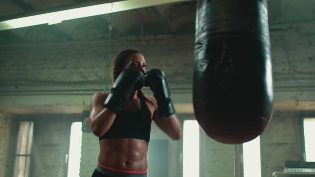 woman boxing punshing bag - sacco per il pugilato video stock e b–roll