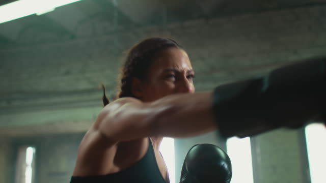 Woman boxing punshing bag video