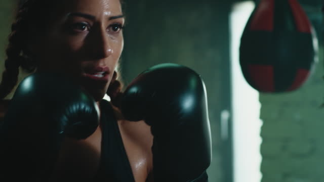 woman boxing punshing bag - irriducibilità video stock e b–roll