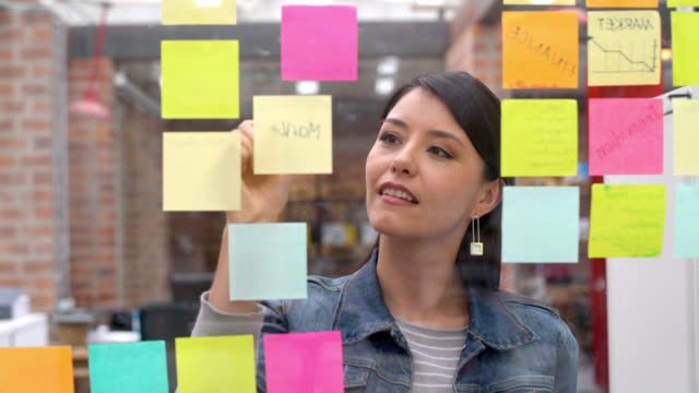 vídeos de stock e filmes b-roll de woman brainstorming at a creative office - papel adesivo