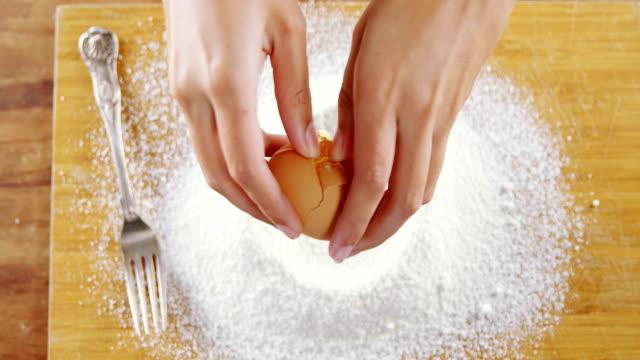 Woman breaking eggs in the flour on wooden board 4k video