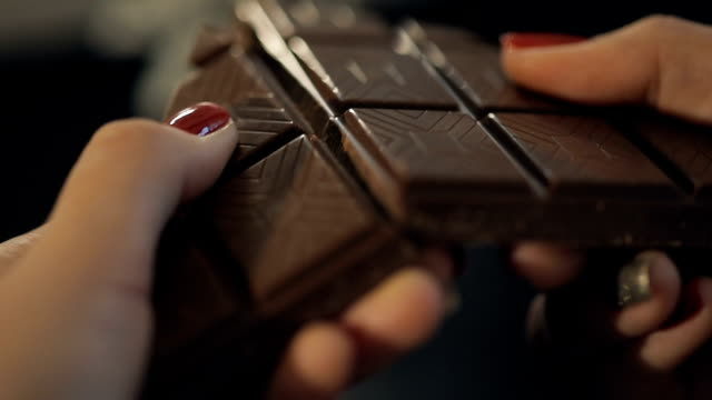 woman breaks chocolate bar. slow motion - cioccolato video stock e b–roll
