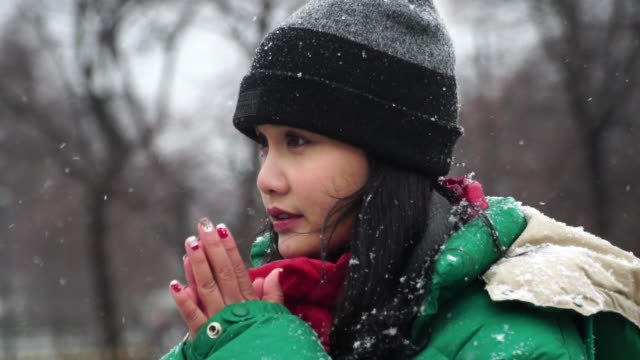 Woman breathing on her hands to keep them warm in winter Portrait of beautiful young woman blowing arms to warm them because of the cold weather in winter shivering stock videos & royalty-free footage