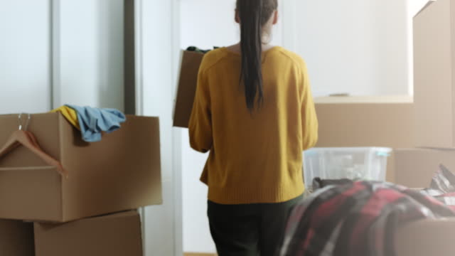 woman bringing in cardboard box with things in her new apartment - appartamento video stock e b–roll