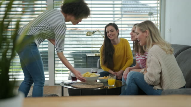 Woman bringing snacks to the table Woman bringing snacks her friends sitting on the couch potato chip stock videos & royalty-free footage