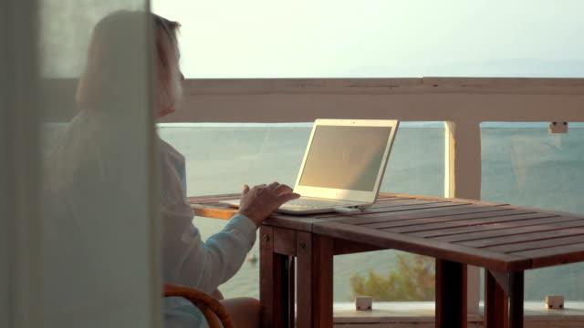 donna di navigazione internet sul portatile utilizzando mobile - tavolo legno video stock e b–roll