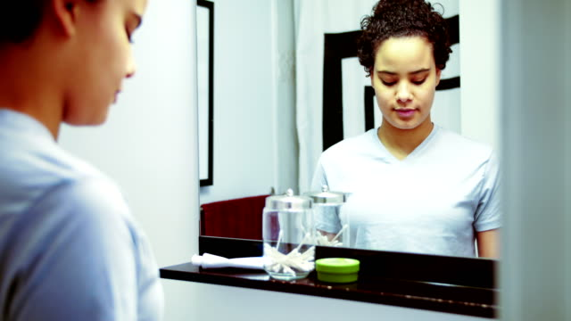 Woman brushing her teeth in front of the mirror 4k video
