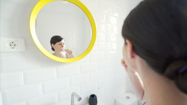 Woman brushing teeth. video