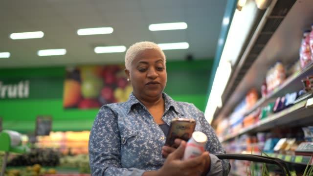 vidéos et rushes de femme achetant au supermarché utilisant le téléphone mobile - 40 44 ans